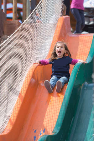screaming girl: Adorable screaming girl on bright chute at playground