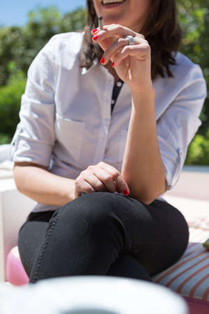 crossed cigarette: Close-up of smiling unrecognizable woman smoking cigarette
