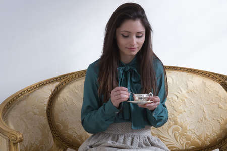 Beautiful young woman sitting on vintage sofa and holding cup of tea while looking down Stock Photo
