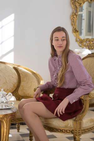 thoughful: Thoughful and calm woman with long hair in elegant clothes looking down while sitting on golden chair. Stock Photo