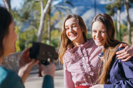 taking photo: Unrecognizable woman with old camera taking photo of smiling girlfriends