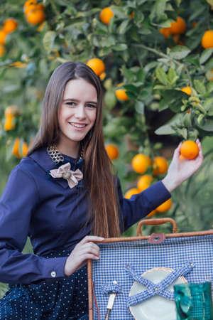 Beautiful young woman holding orange on orange tree branch