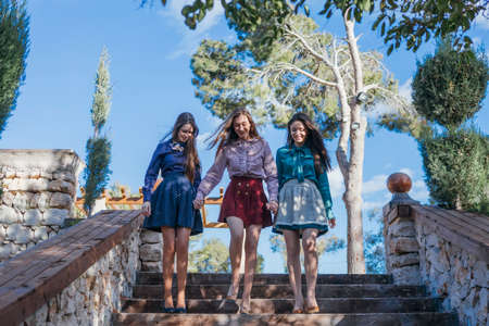 down the stairs: sonriendo novias elegantes vigilia por las escaleras en el jardín