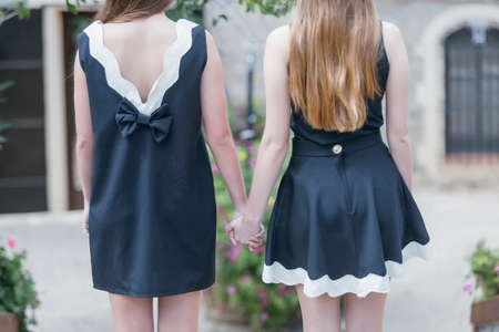 incognito: back view of two young women in stylish black and white dresses