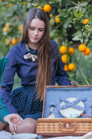 woman looking down: Elegant young woman looking down while sitting on picnic in garden