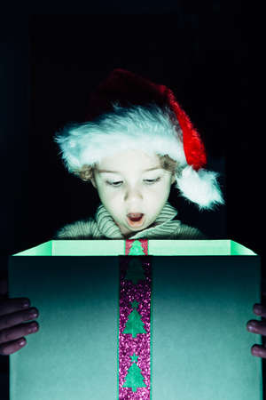 boca abierta: Portrait of surprised boy in Santa hat looking down at Christmas present with open mouth
