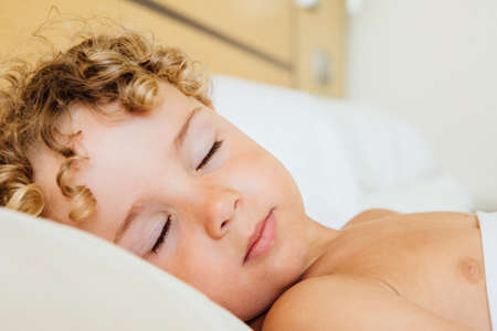 angel alone: Close-up of cute boy with blond curly hair sleeping on bed