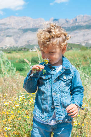 Portrait of lovely boy with blond windy hair smelling a flower against of landscape in sunlight