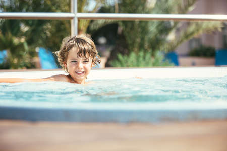 Portrait of adorable curly-haired boy in jacuzzi in sunlight
