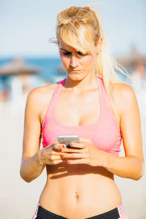 sportswoman: Portrait of young angry sportswoman using mobile phone on beach