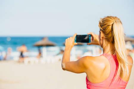 cola mujer: Vista trasera de una mujer rubia irreconocible con la cola que toma la fotografía a través del teléfono móvil en la playa Foto de archivo