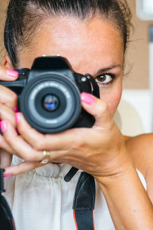 grizzle: Portrait of adult woman holding professional camera