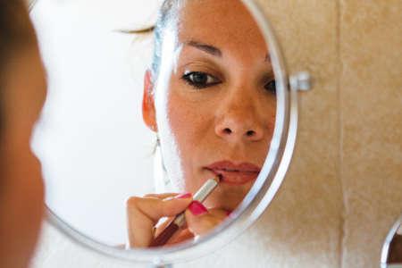 lip pencil: Mirror reflection of beautiful adult woman put on lip pencil Stock Photo