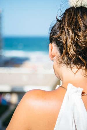 cola mujer: Vista posterior del hombro desnudo de la mujer morena con cola contra de la playa y el mar en el cielo azul.