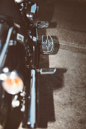 throttle: Close-up of motorbike side with throttle pedal against asphalt ground