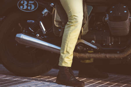 sitting on the ground: Close up of unrecognizable man in pants and boots sitting on bike with feet on ground Stock Photo