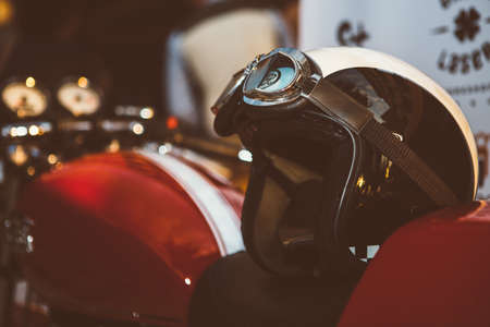 Motorbike exhibition. Black and white vintage helmet with glasses on bike seat