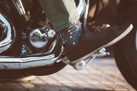 throttle: Close-up of foot in polka dot sock and leather shoe on throttle pedal of bike