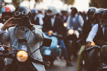 Menigte van elegante fietsers die moto's berijden. man nemen foto met behulp van de telefoon op de voorgrond.