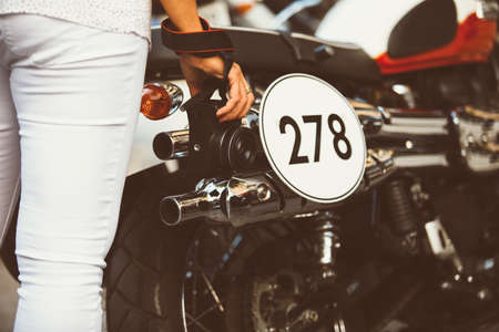 number plate: unrecognizable female photographer with camera in hand at bike with number plate