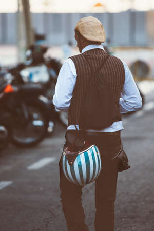 the distinguished: ALICANTE, SPAIN - SEPTEMBER 25, 2016: Back view of a man is holding bright stripy bike helmet and backpack on the Distinguished Gentlemans Ride day, a global fundraiser for prostate cancer and mens health investigation
