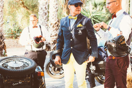 the distinguished: ALICANTE, SPAIN - SEPTEMBER 25, 2016: Men dressed in dapper styles are talking while they are holding their helmets on the Distinguished Gentlemans Ride day, a global fundraiser for prostate cancer and mens health investigation Editorial