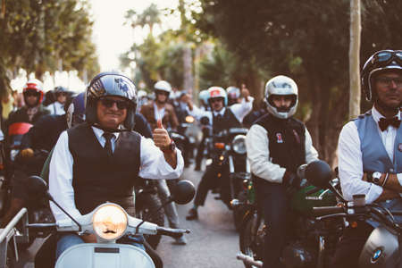 the distinguished: ALICANTE, SPAIN - SEPTEMBER 25, 2016: Middle aged rider on motorcycle is ready to start the race near a big group of riders and showing his thumb up on the Distinguished Gentlemans Ride day, a global fundraiser for prostate cancer and mens health invest Editorial