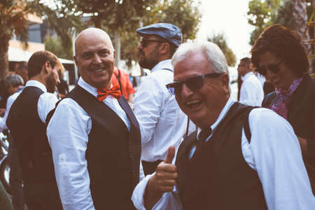 the distinguished: ALICANTE, SPAIN - SEPTEMBER 25, 2016: Smiling middle aged man is looking at camera while his friend is showing the thumb up on the Distinguished Gentlemans Ride day, a global fundraiser for prostate cancer and mens health investigation