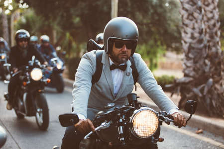 the distinguished: ALICANTE, SPAIN - SEPTEMBER 25, 2016: Male rider on motorcycle is driving his motorbike and is wearing helmet and leather gloves on the Distinguished Gentlemans Ride day, a global fundraiser for prostate cancer and mens health investigation