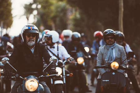the distinguished: ALICANTE, SPAIN - SEPTEMBER 25, 2016: Middle aged rider on motorcycle is ready to start the race near a big group of riders on the Distinguished Gentlemans Ride day, a global fundraiser for prostate cancer and mens health investigation
