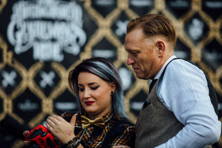 the distinguished: ALICANTE, SPAIN - SEPTEMBER 25, 2016: Stylish woman photographer is showing his work on her camera to a man on the Distinguished Gentlemans Ride day, a global fundraiser for prostate cancer and mens health investigation. Editorial