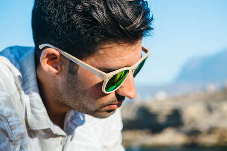 Portrait of stylish sad man with sunglasses looking down outdoors Stock Photo