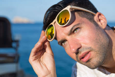 Portrait of handsome guy raises sunglasses and looking away