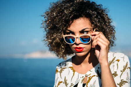 strictly: Portrait of mixed race beautiful girl with curly hair strictly looking over sunglasses