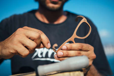 Close up of unrecognizable man treats wooden rim glassses with screwdriver