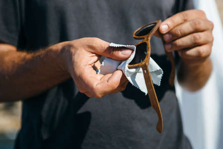 Unrecognizable man polishing lens of elegance wooden sunglasses with soft napkin Standard-Bild