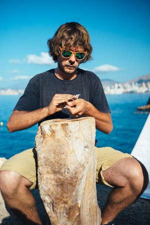 Portrait of bearded man in sunglasses sitting on seashore and treats wooden rim glasses