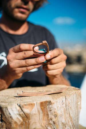 Close up of unrecognizable male master treats handmade wooden rim glasses