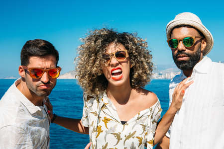 mixed race girl: Two stylish men and mixed race girl in sunglasses looking at camera. Woman is shouting