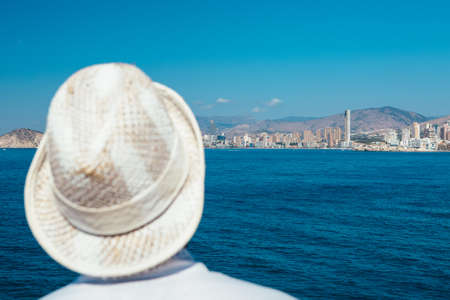 unrecognizable person: Back view of unrecognizable person in straw hat standing against seascape
