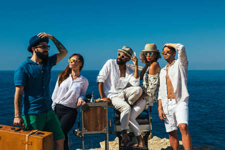 barber chair: Portrait of elegance multiethnic group of people posing in sunglasses on antique barber chair with suitcase Stock Photo