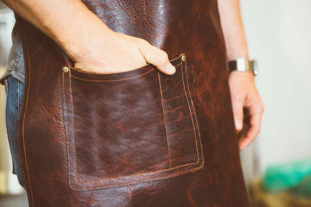 incognito: Close-up of unrecognizable coffee roaster holding hand in leather pocket of apron