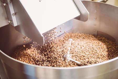 Fresh roasted coffee beans falling in roasting machine in daylight