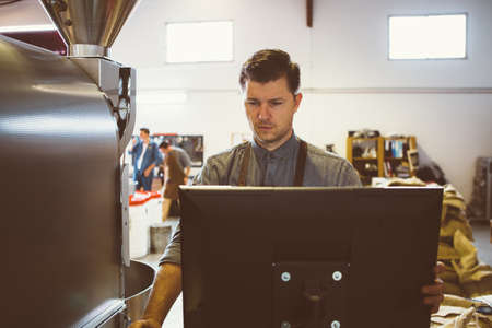 Roaster: Portrait of serious coffee roaster using computer at factory Stock Photo