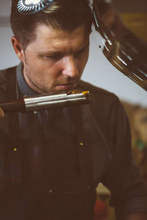 Roaster: Portrait of professional roaster holding probe of fresh roasted coffee beans and looking at it Stock Photo