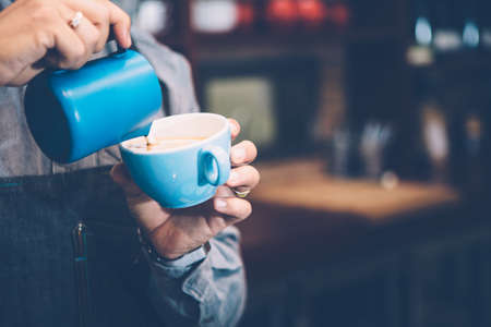 Close-up of unrecognizable man preparing coffee in blue cup with pitcher