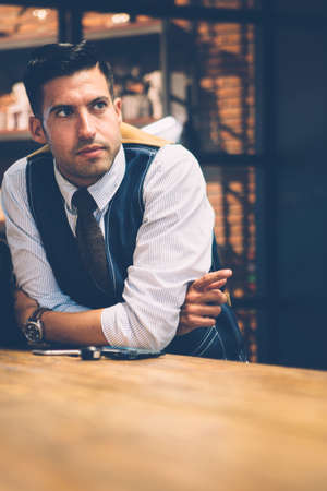 Portrait of good-looking man in elegant tie and waistcoat leaning on table and pointing with index finger. Stock Photo