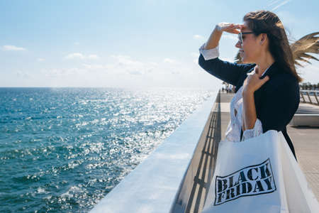 far away look: Stylish woman looking far away while standing at seaside and holding Black Friday bags.