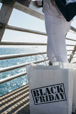 incognito: View of incognito woman standing next to Black Friday purchases on sea front border.Copyspace