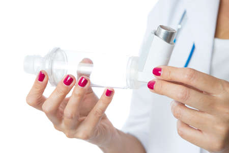 inhaled: Close up of the hands of a female doctor holding a pressurized cartridge inhaler placed on an inhalation chamber on a medical demostration - Isolated on a white background Stock Photo